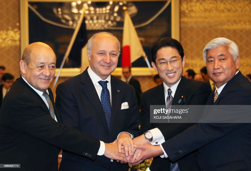French Minister of Defense Jean-Yves Le Drian, French Foreign Minister Laurent Fabius, Japanese Foreign Minister Fumio Kishida and Defense Minister Gen Nakatani shake hands during a two-plus-two meeting in Tokyo on March 13, 2015. AFP PHOTO / POOL / Koji Sasahara