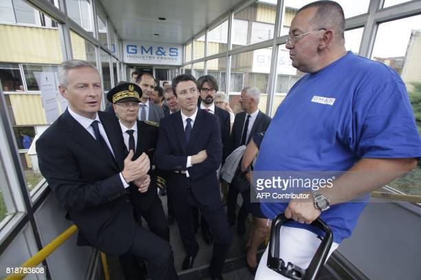 French Minister of Economy Bruno Le Maire and French Junior Economy Minister Benjamin Griveaux speak to an employee of French auto parts manufacturer...