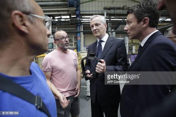 French Minister of Economy Bruno Le Maire and French Junior Economy Minister Benjamin Griveaux listen to an employee of French auto parts...