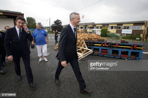 French Minister of Economy Bruno Le Maire and French Junior Economy Minister Benjamin Griveaux walk past a pile of pallets as they visit the site of...