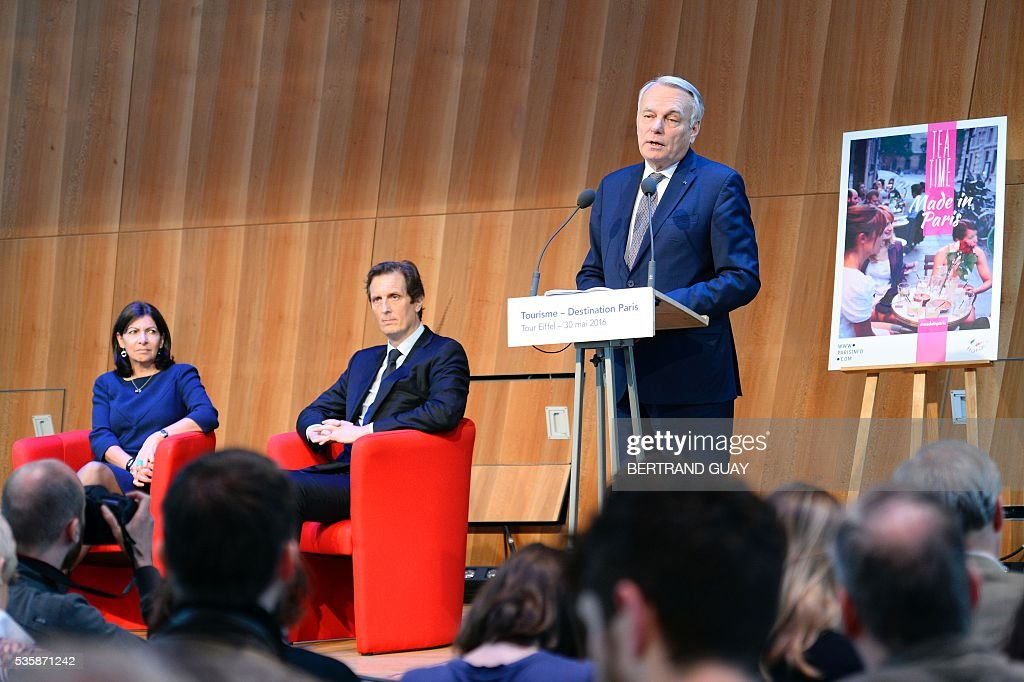 French Minister of Foreign Affairs Jean-Marc Ayrault (R), next to Paris Mayor Anne Hidalgo (L) and Ile-de-France region's first vice-president Jerome Chartier, delivers a speech during a press conference about tourism in Paris on May 30, 2016 in Paris. / AFP / BERTRAND