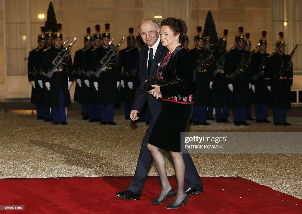 French Minister of Foreign Affairs, Laurent Fabius (L) an unidentified person arrive, at the Elysee palace in Paris, before a state dinner as part of a two-day state visit of Italian President Giorgio Napolitano, on November 21, 2012.