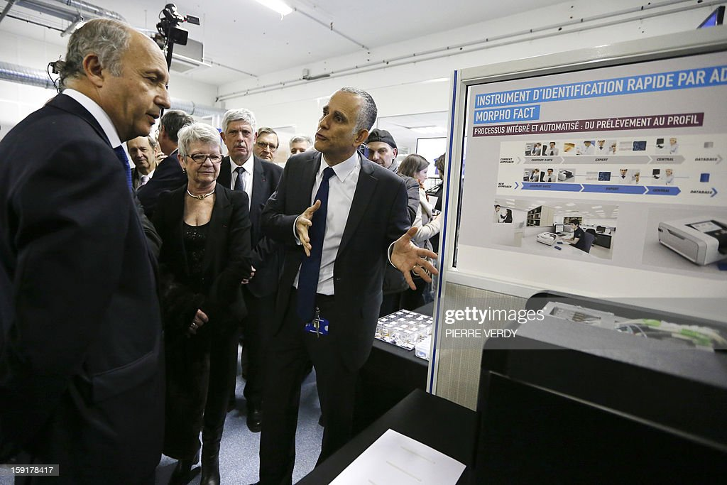 French Minister of Foreign Affairs, Laurent Fabius (L) listens to explanations during a visit on January 9, 2013 to the French aerospace and defence group Safran's research center in Osny, northwest of Paris.