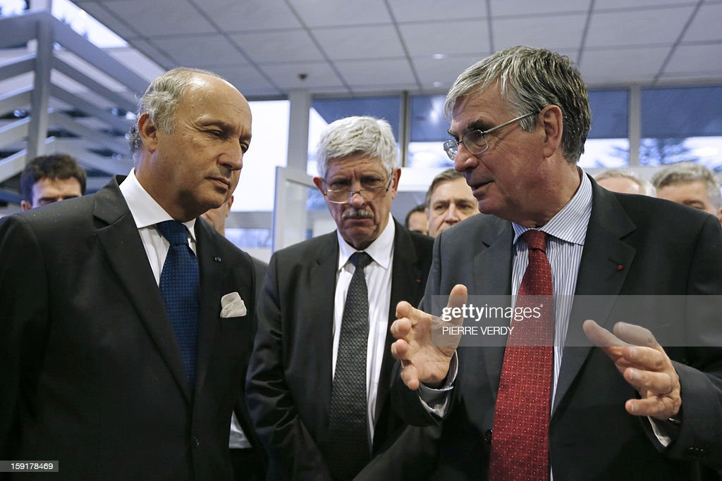 French Minister of Foreign Affairs, Laurent Fabius (L) listens to the CEO of French aerospace and defence group Safran, Jean-Paul Herteman (R) on January 9, 2013 during a visit to the group's research center in Osny, northwest of Paris. At center is seen Jean-Paul Jainsky, the CEO of Morpho, specialized in products dedicated to law enforcement and border control.