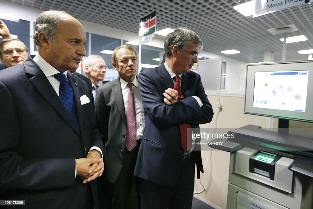 French Minister of Foreign Affairs, Laurent Fabius (L) looks at a screen showing a fingerprint detection system, beside the French aerospace and defence group Safran, Jean-Paul Herteman (R) on January 9, 2013 during a visit to the group's research center in Osny, northwest of Paris.