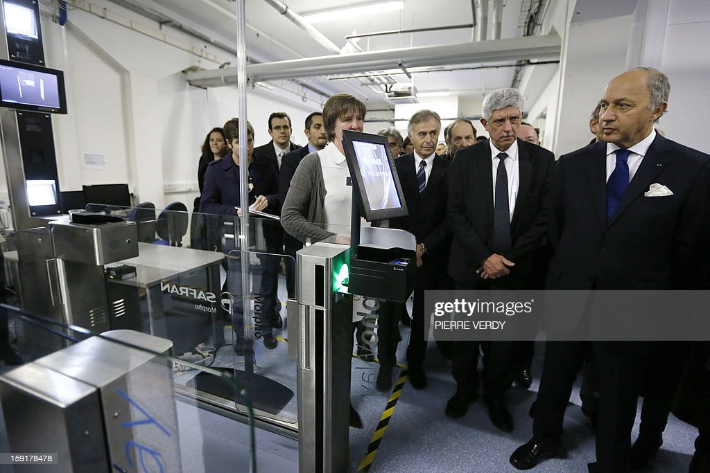 French Minister of Foreign Affairs, Laurent Fabius (R) looks at electronic security equipment during a visit to the research center of French aerospace and defence group Safran, on January 9, 2013 in Osny, northwest of Paris. At second right is seen Jean-Paul Jainsky, the CEO of Morpho, specialized in products dedicated to law enforcement and border control.