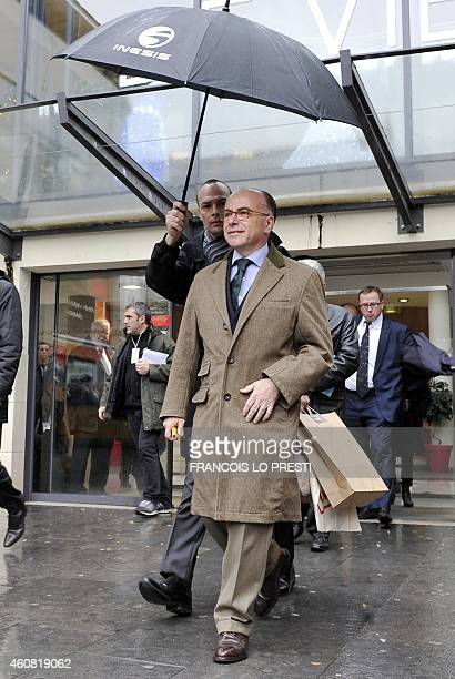 French minister of Interior Bernard Cazeneuve gets out of a shopping mall on December 24 2014 in Calais northern France The new Jules Ferry reception...