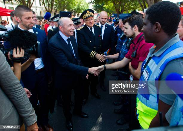French Minister of Interior Gerard Collomb shakes hands with a 'La Vuelta' worker prior to the start of the first stage of the 72nd edition of 'La...