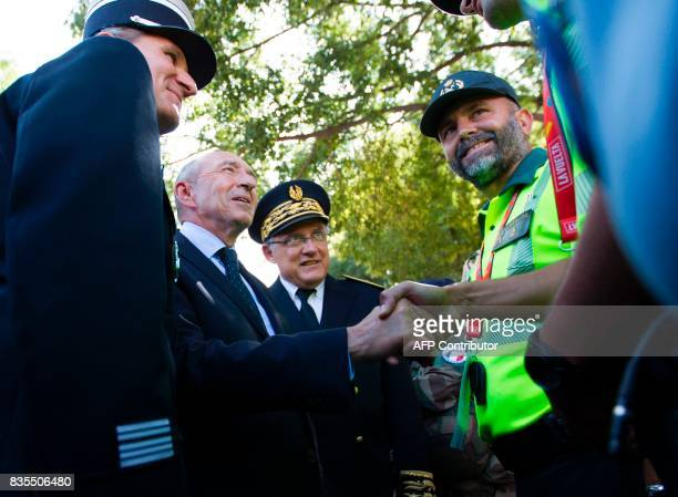 French Minister of Interior Gerard Collomb shakes the hand of Spanish Civil Guard member prior to the start of the first stage of the 72nd edition of...