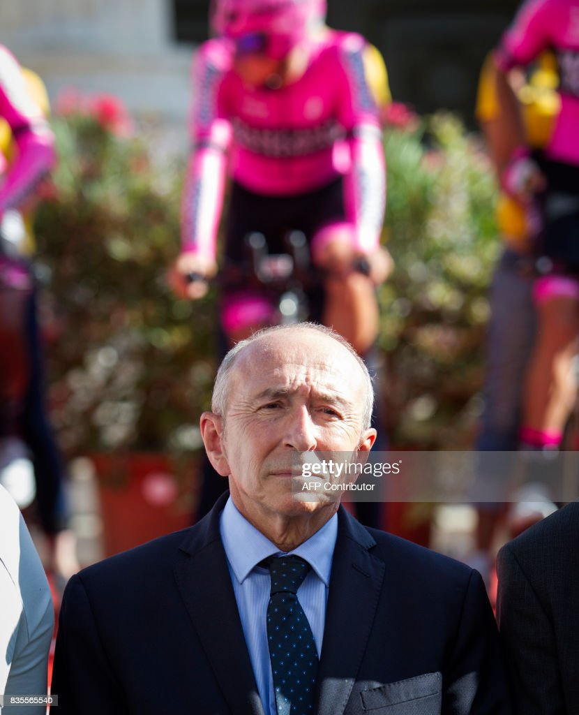 French Minister of Interior Gerard Collomb stands during a minute's silence in solidarity with Barcelona following a vehicle attack on the city, prior to the start of the first stage of the 72nd edition of 'La Vuelta' Tour of Spain cycling race in Nimes on August 19, 2017. Twin vehicle attacks on August 17, left 14 dead and over 100 more injured in a bustling tourist area of Barcelona and the nearby Spanish seaside resort of Cambrils, affecting people from some three dozen countries. /