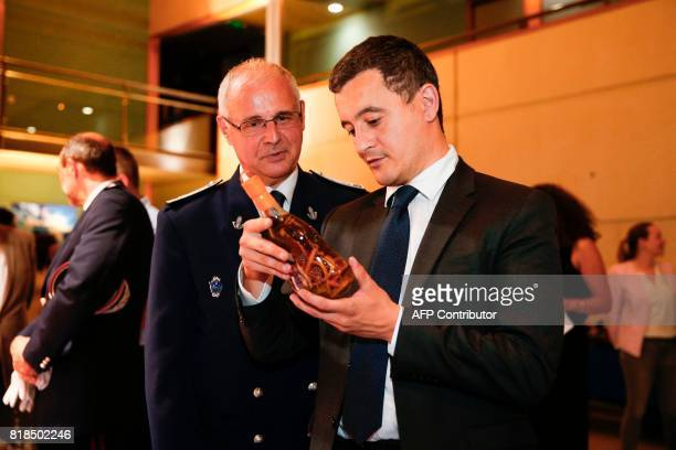 French Minister of Public Action and Accounts Gerald Darmanin and Head of RoissyCharles de Gaulle airport's Customs Philippe Legue look at a bottle...