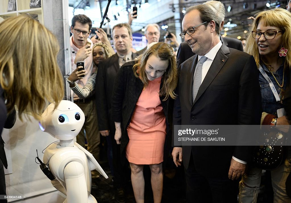 French Minister of State for the Digital Sector Axelle Lemaire (C) and French President Francois Hollande (2nd R) stand next to the IBM Watson powered robot during a visit to the Viva technology event in Paris on June 30, 2016. / AFP / POOL / STEPHANE