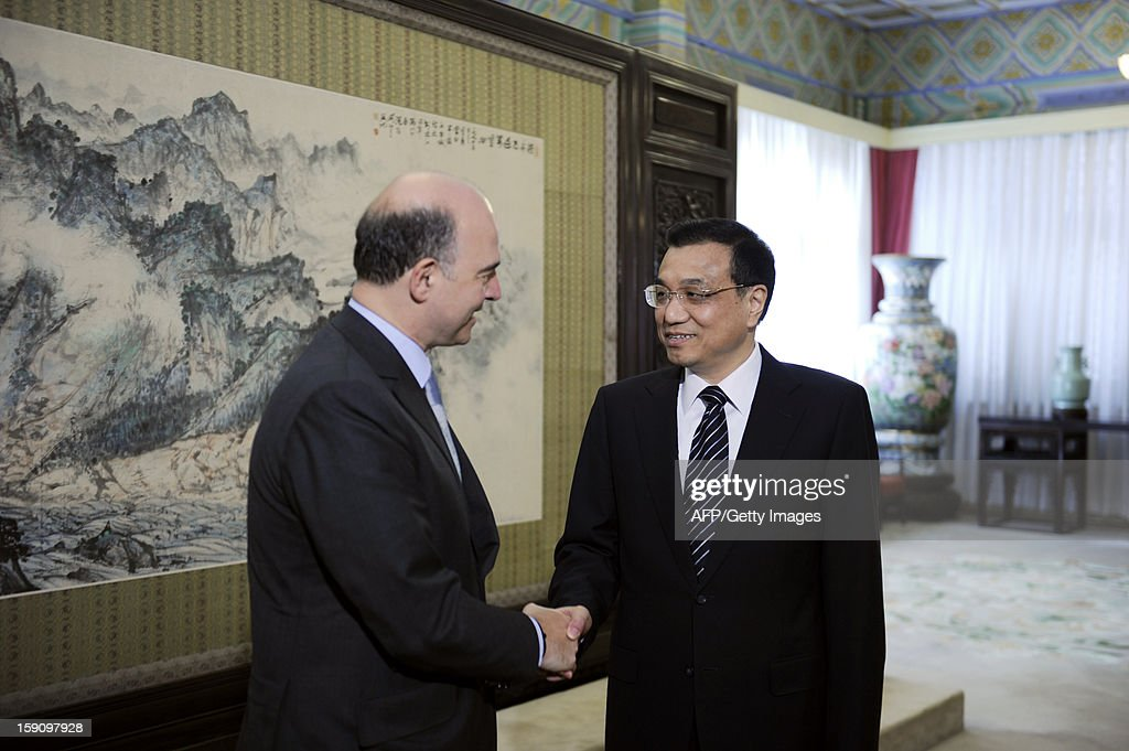 French Minister of the Economy Pierre Moscovici (L) shakes hands with Chinese Vice Premier Li Keqiang (R) at the Zhongnanhai leaderships compound in Beijing on January 8, 2013. Moscovici started his a two day visit to China on January 7, 2013. AFP PHOTO / POOL / WANG ZHAO