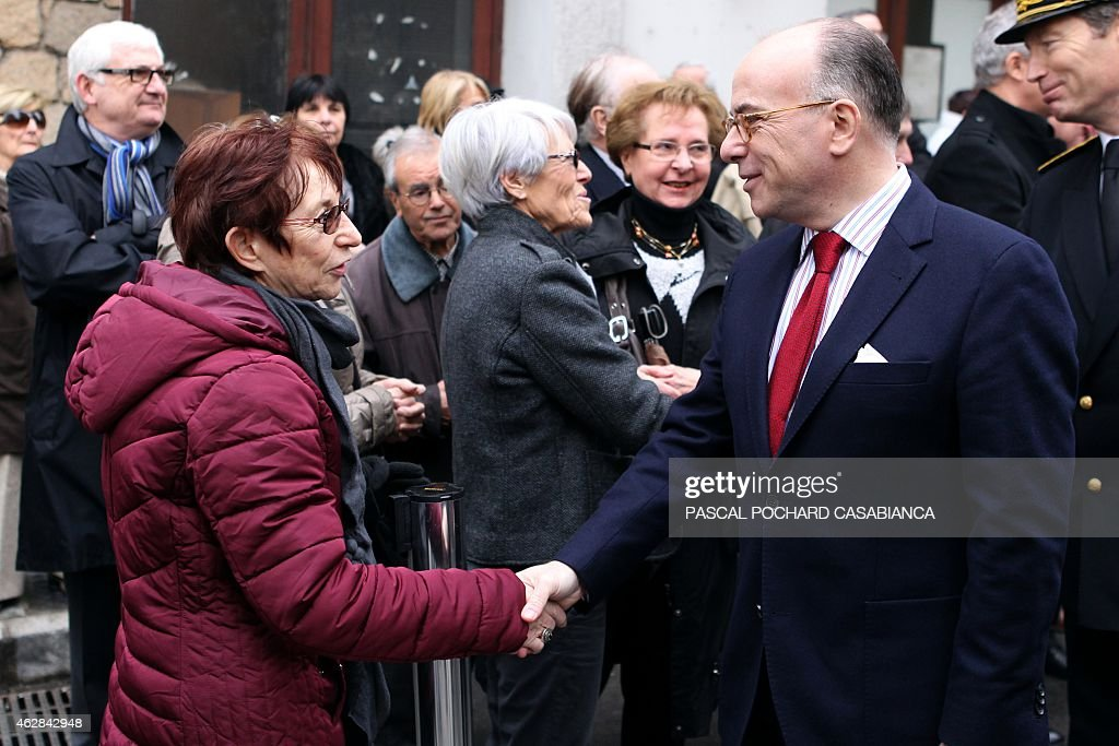 French Minister of the Interior <a gi-track='captionPersonalityLinkClicked' href=/galleries/search?phrase=Bernard+Cazeneuve&family=editorial&specificpeople=4205153 ng-click='$event.stopPropagation()'>Bernard Cazeneuve</a> (R) shakes hands to an inhabitant after a ceremony in tribute to murdered prefect <a gi-track='captionPersonalityLinkClicked' href=/galleries/search?phrase=Claude+Erignac&family=editorial&specificpeople=883251 ng-click='$event.stopPropagation()'>Claude Erignac</a>, marking the 17th anniversary of his death, at the shooting site on February 6, 2015 in Ajaccio, French Mediterranean island of Corsica. Prefect Erignac was shot three times in the back of the head as he walked to meet his wife at a concert hall in Corsica's capital Ajaccio on February 6, 1998.