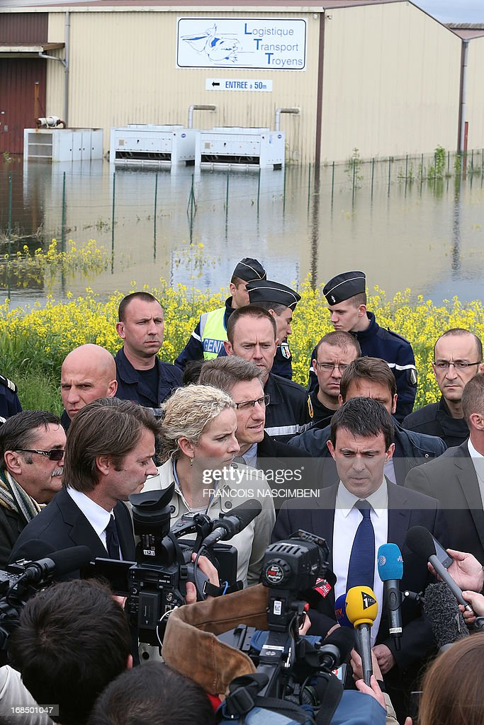 French Minister of the Interior Emmanuel Valls (Front R) and French Minister of the Environment Delphine Batho (Front 3rd L) speak with journalists after meeting with firefighters and emergency services workers on May 10, 2013, during a visit to Bucheres, a town in north-central France which was recently affected by floods. The floods which occurred this past week in the Aube region of France came about after heavy rainfall caused the Seine river to overflow. The tide today finally began to come down across the region.