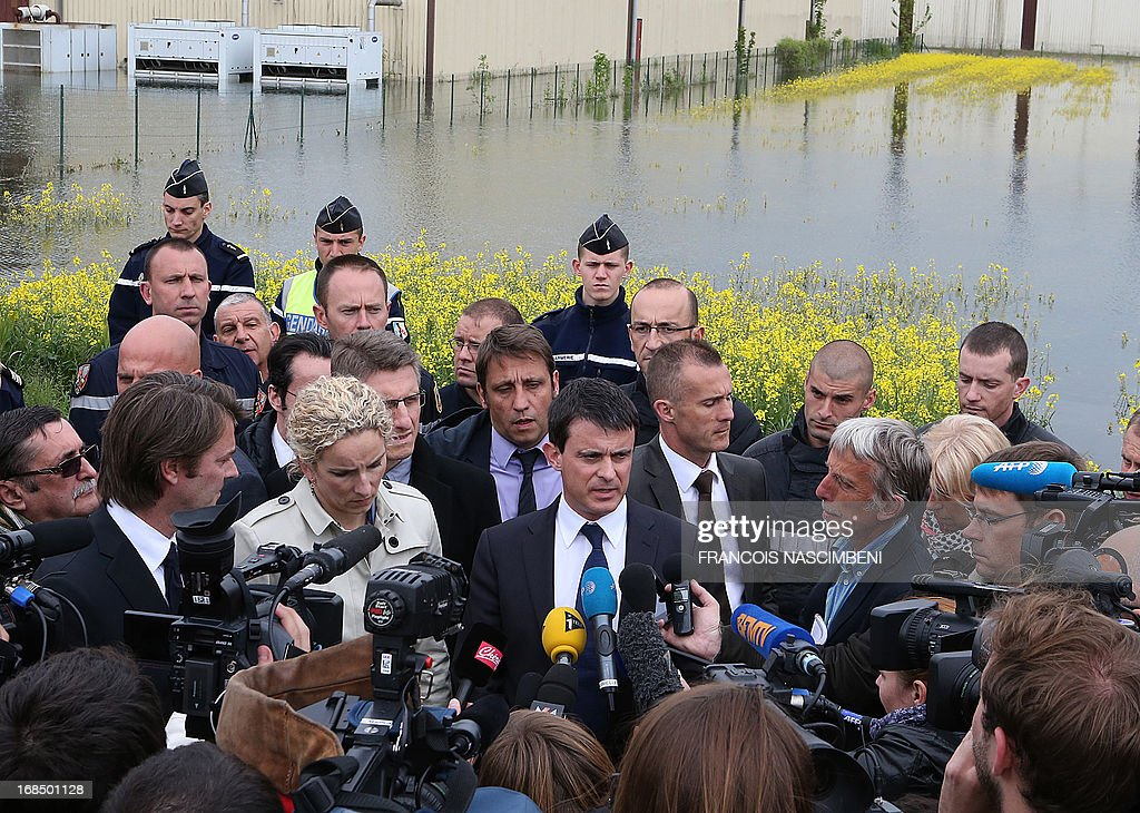 French Minister of the Interior Emmanuel Valls (Front C) and French Minister of the Environment Delphine Batho (Front 3rd L) speak with journalists after meeting with firefighters and emergency services workers on May 10, 2013, during a visit to Bucheres, a town in north-central France which was recently affected by floods. The floods which occurred this past week in the Aube region of France came about after heavy rainfall caused the Seine river to overflow. The tide today finally began to come down across the region.