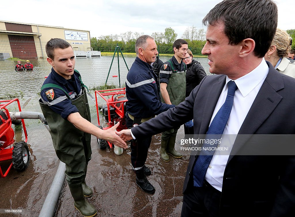 French Minister of the Interior Emmanuel Valls greets a group of firefighters and emergency services workers on May 10, 2013, during a visit to Bucheres, a town in north-central France which was recently affected by floods. The floods which occurred this past week in the Aube region of France came about after heavy rainfall caused the Seine river to overflow. The tide today finally began to come down across the region.
