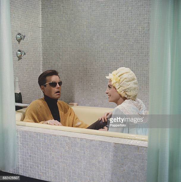 French model and actress Capucine pictured sitting in a bath with American actor Robert Wagner in a scene from the film The Pink Panther in Rome...
