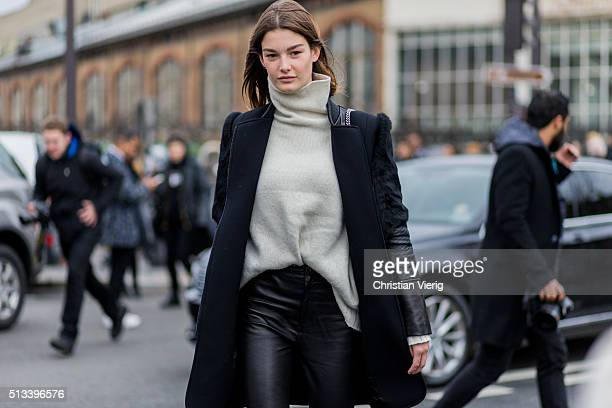 French model Ophelie Guillermand wearing a creme turtleneck and a navy wool coat with leather and a black leather pants outside Dries van Noten...