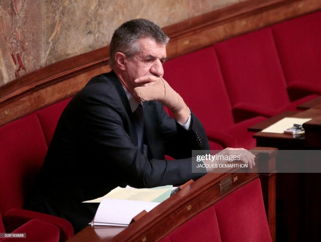 French MoDem party MP Jean Lassalle, his hand bandaged, looks on at the French National Assembly in Paris on February 9, 2016, as French lawmakers examined proposed changes to the constitution. France's lower house of parliament is to vote on plans to enshrine a state of emergency into the constitution, including a controversial measure to strip French nationality from those convicted of terrorism and serious crimes. / AFP / JACQUES DEMARTHON