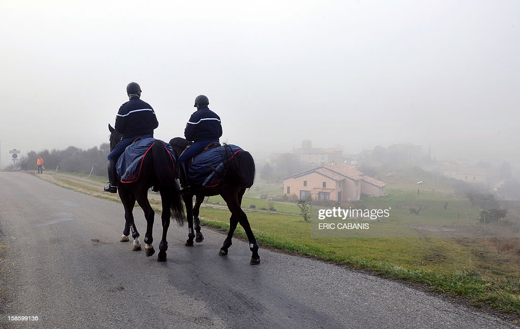 French mounted police patrol on December 20, 2012 in the French southwestern village of Bugarach, near the 1,231 meter high peak of Bugarach - one of the few places on Earth some believe will be spared when the world allegedly ends according to claims regarding the ancient Mayan calendar. French authorities have pleaded with New Age fanatics, sightseers and media crews not to converge on the tiny village. AFP PHOTO / ERIC CABANIS