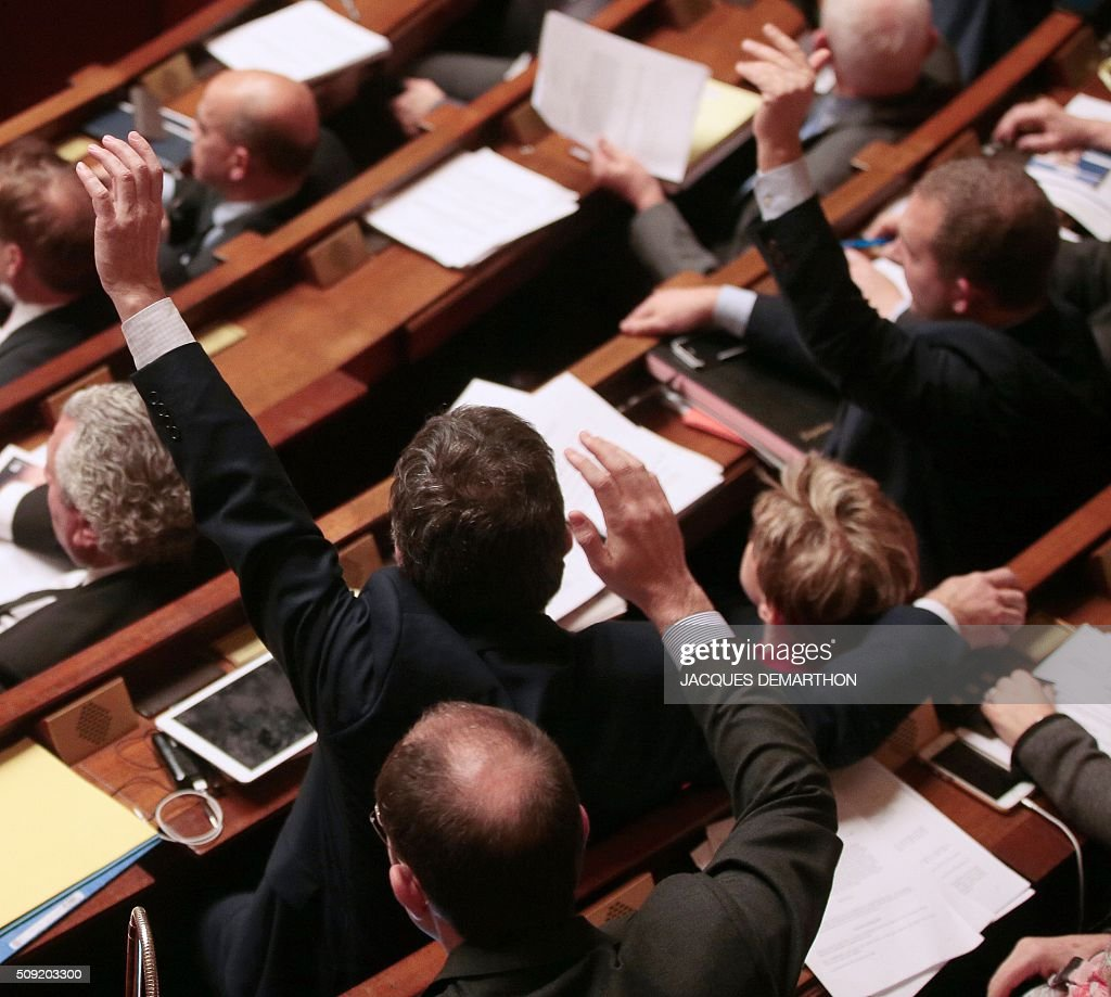 French MPs vote by a show of hands on several proposed amendments to the constitution at the French National Assembly in Paris on February 9, 2016. France's lower house of parliament is to vote on plans to enshrine a state of emergency into the constitution, including a controversial measure to strip French nationality from those convicted of terrorism and serious crimes. / AFP / JACQUES DEMARTHON