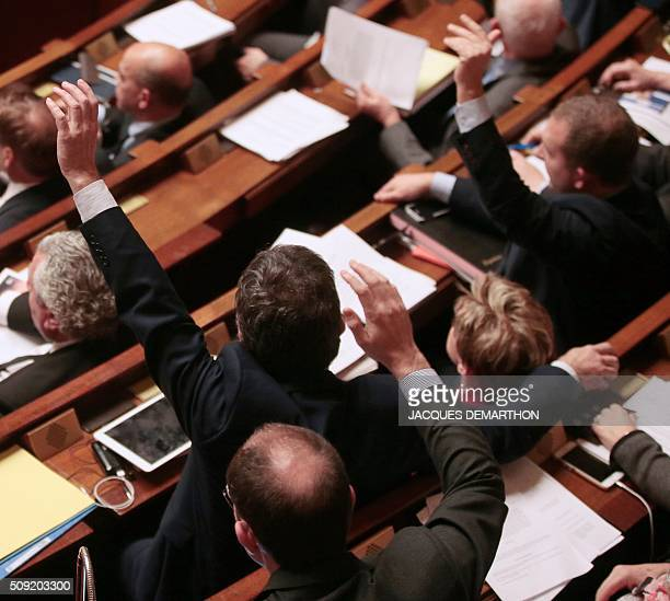 French MPs vote by a show of hands on several proposed amendments to the constitution at the French National Assembly in Paris on February 9 2016...