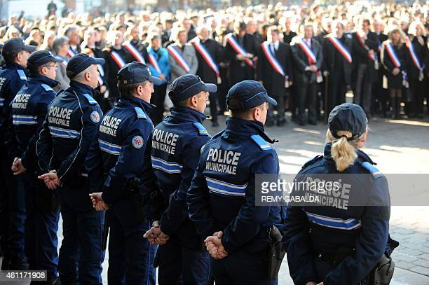 French municipal police officers and local representatives observe a minute of silence in front of the city hall in Toulouse on January 8 to pay...