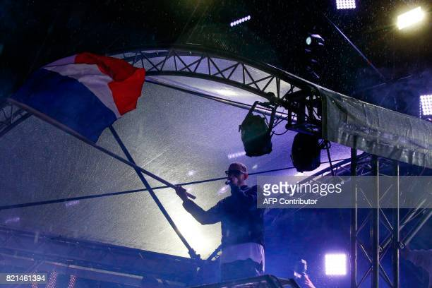 French musician DJ Snake whose real name is William Grigahcine wave a French flag as he performs during the Lollapalooza music festival at the...
