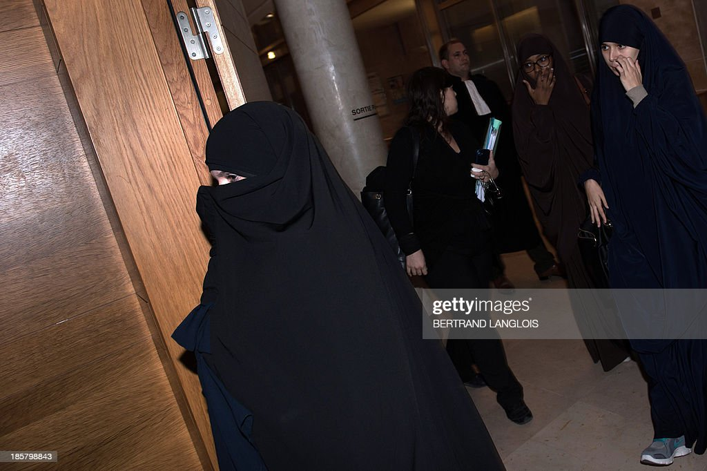 French Muslim woman Louise-Marie Suisse (L), accused of having bitten a policewoman during an idendity check in Marseille, enters on October 25, 2013 the court of appeal wearing a niqab in the courthouse of Aix-en-Provence, southern France.