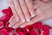 Modern french nails manicure on young girl hands. Hands of girl is on red rose petals in beauty studio. Beauty and Manicure concept. Close up, selective focus