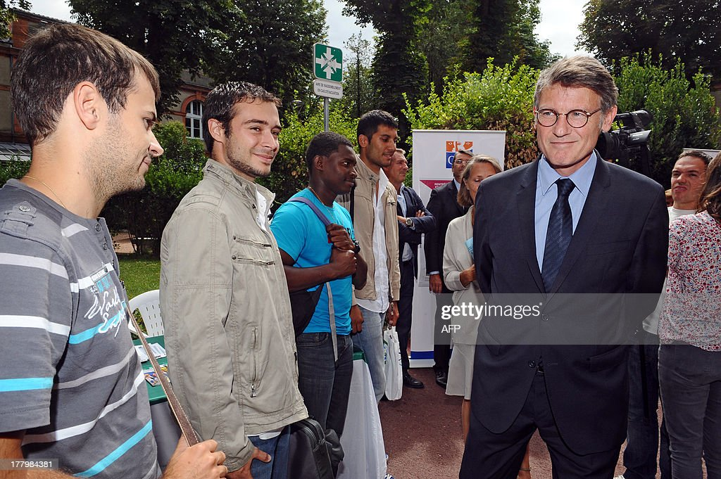 French National Education minister Vincent Peillon (R) arrives to take part in a meeting with trainee teachers at the Faculty of Social Sciences in Toulouse, southern France, on August 26, 2013.