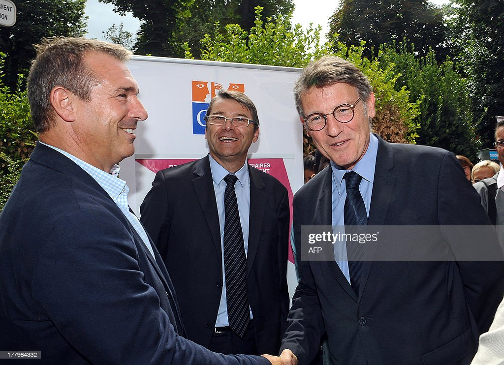 French National Education minister Vincent Peillon (R) shakes hands with former rugby player Eric Bonneval (L) before taking part in a meeting with trainee teachers at the Faculty of Social Sciences in Toulouse, southern France, on August 26, 2013.