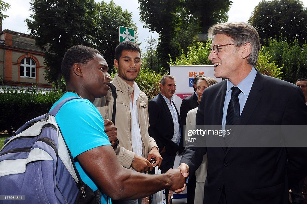 French National Education minister Vincent Peillon (R) shakes hands with a teacher before taking part in a meeting with trainee teachers at the Faculty of Social Sciences in Toulouse, southern France, on August 26, 2013.