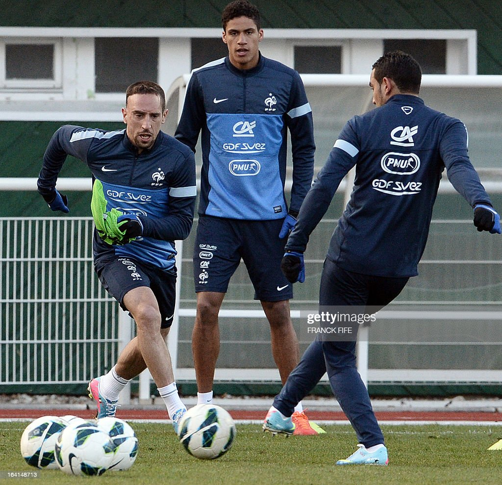 French national football team forward Franck Ribery (L) vies with forward Dimitri Payet (R) eyed by defender Raphael Varane (C) during a training session in Clairefontaine-en-Yvelines, near Paris on March 20, 2013, two days ahead of a World Cup 2014 qualifying football match against Georgia to be held at the stade de France in Saint-Denis, north of Paris. AFP PHOTO / FRANCK FIFE