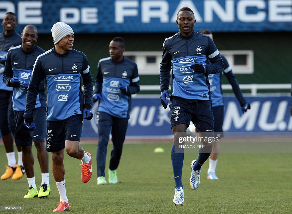 French national football team forward Loic Remy (L) and defender Mapou Nyanga Mbiwa (R) take part in a training session in Clairefontaine-en-Yvelines, near Paris on March 20, 2013, two days ahead of a World Cup 2014 qualifying football match against Georgia to be held at the stade de France in Saint-Denis, north of Paris. AFP PHOTO / FRANCK FIFE