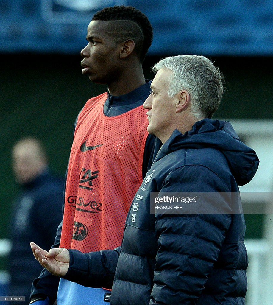 French national football team head coach Didier Deschamps (R) speaks with midfielder Paul Pogba during a training session in Clairefontaine-en-Yvelines, near Paris, on March 20, 2013, two days ahead of a World Cup 2014 qualifying football match against Georgia to be held at the stade de France in Saint-Denis, north of Paris. AFP PHOTO / FRANCK FIFE