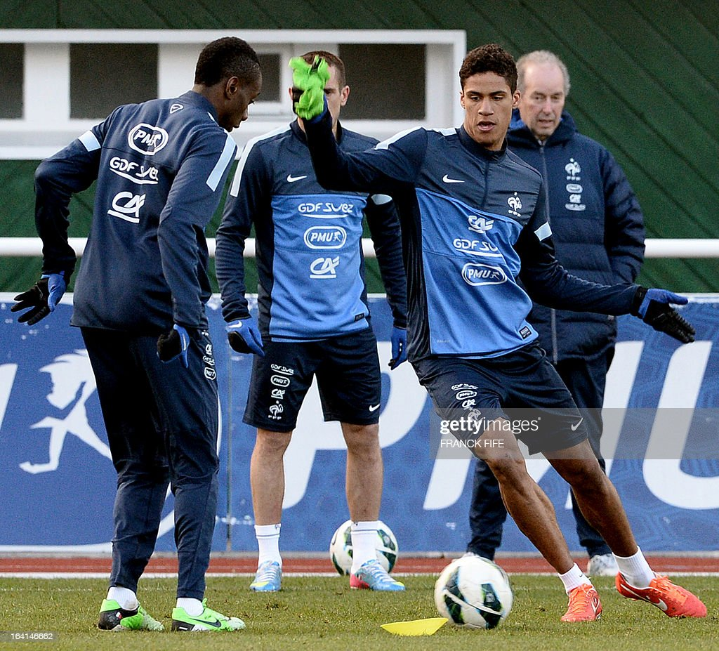 French national football team midfielder Blaise Matuidi (C) vies with midfielder Raphael Varane (R) during a training session in Clairefontaine-en-Yvelines, near Paris, on March 20, 2013, two days ahead of a World Cup 2014 qualifying football match against Georgia to be held at the stade de France in Saint-Denis, north of Paris.