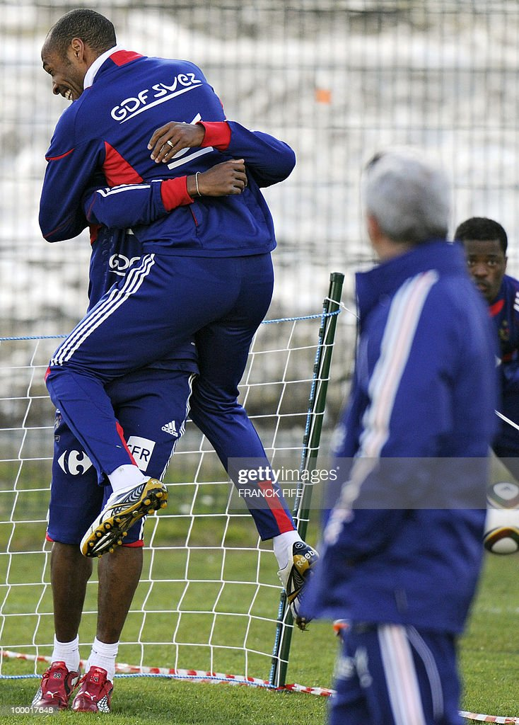 French national football team's captain Thierry Henry (C) jokes with Nicolas Anelka (L), next to French coach Raymond Domenech (R) during a training session, on May 20, 2010 in Tignes, French Alps, as part of their altitude training in preparation for the 2010 World cup in South Africa. France will play Uruguay in Capetown in its group A opener match on June 11.