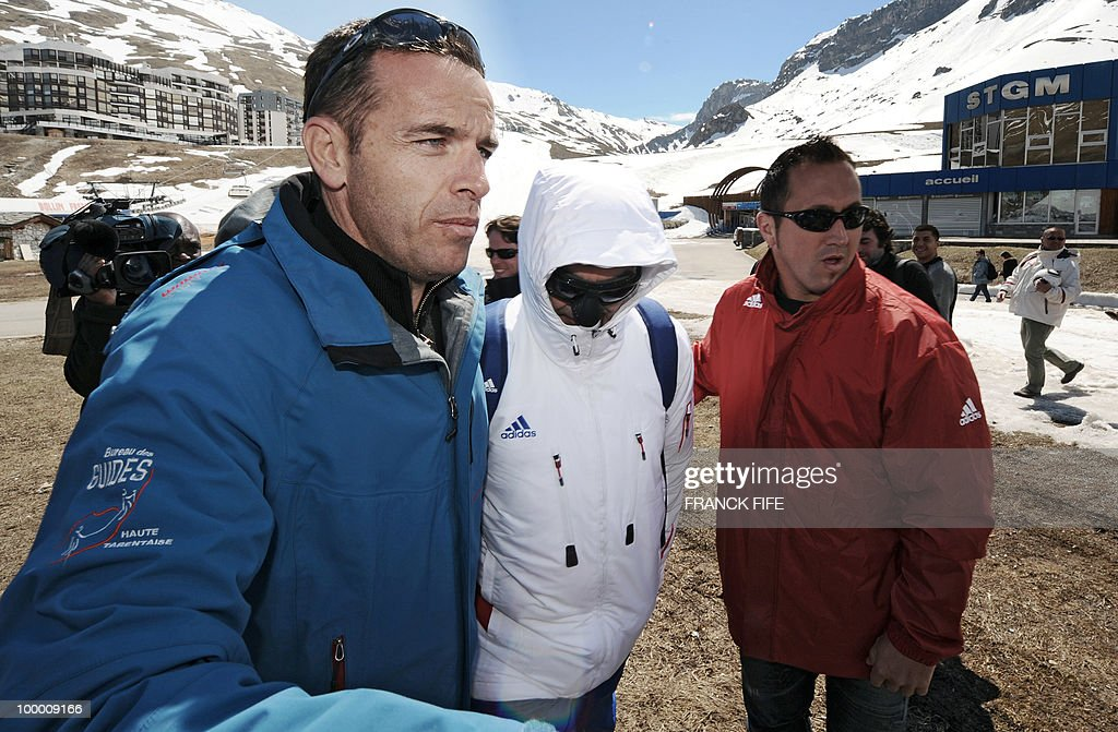 French national football team's coach Raymond Domenech (C) wears a sunmask as he arrives with moutain guides in Tignes, French Alps, on May 20, 2010 after having spent the night with his team at the top of a glacier. The French national team slept in altitude last night, as part of their altitude training in preparation for the 2010 World cup in South Africa.