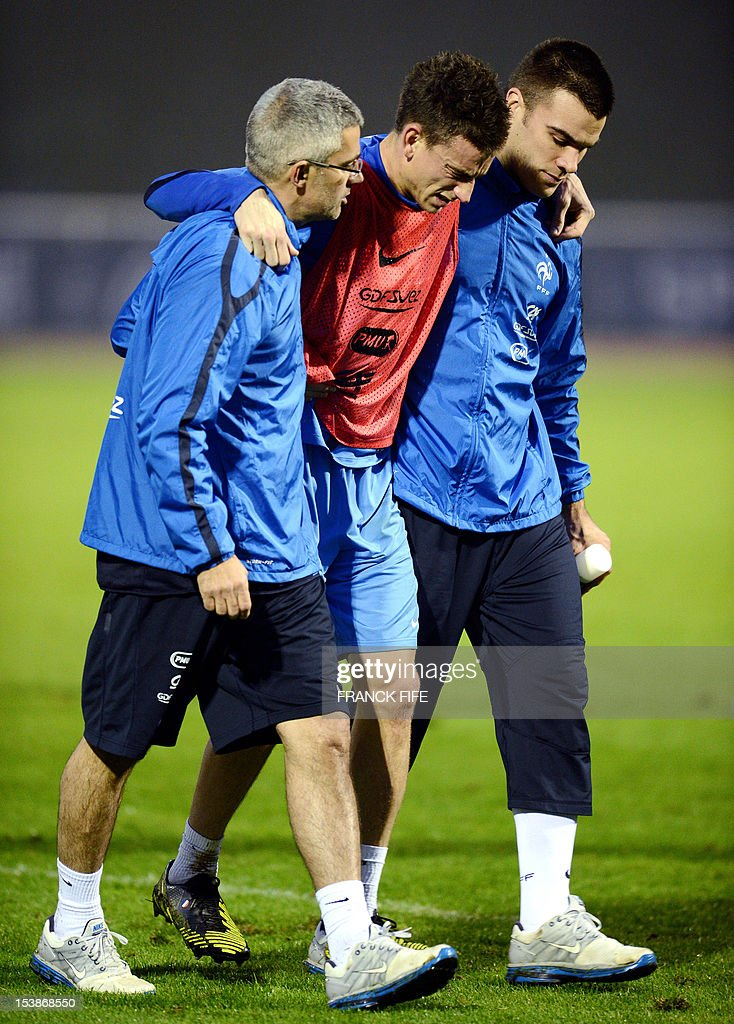 French national football team's defender Laurent Koscielny (C) is helped by a medical staff member during a training session in Clairefontaine-en-Yvelines, outside Paris, on October 10, 2012, two days ahead of the friendly football match France vs Japan. France will play its second World Cup Brazil 2014 qualifying match against Spain on october 16, 2012. AFP PHOTO / FRANCK FIFE