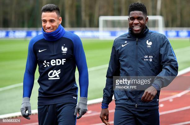 French national football team's defender Samuel Umtiti jokes with midfielder Corentin Tolisso before a training session on March 20 in Clairefontaine...