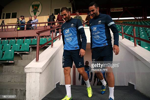 French national football team's forward Karim Benzema and defender Adil Rami arrive to take part in a training session on September 9 on the eve of...