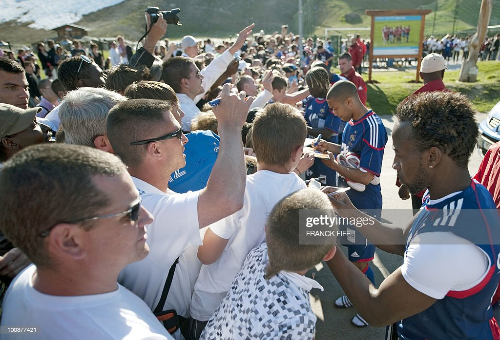 French national football team's forward Sidney Govou (R) signs a autographs after a training session, on May 24, 2010, near Tignes in the French Alps, as part of the preparation for the upcoming World Cup 2010. France will play against Uruguay in Capetown in its group A opener match on June 11.