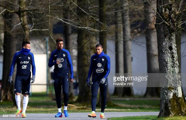 French national football team's midfielder Corentin Tolisso defender Presnel Kipembe and forward Kylian Mbappe arrive for a training session in...