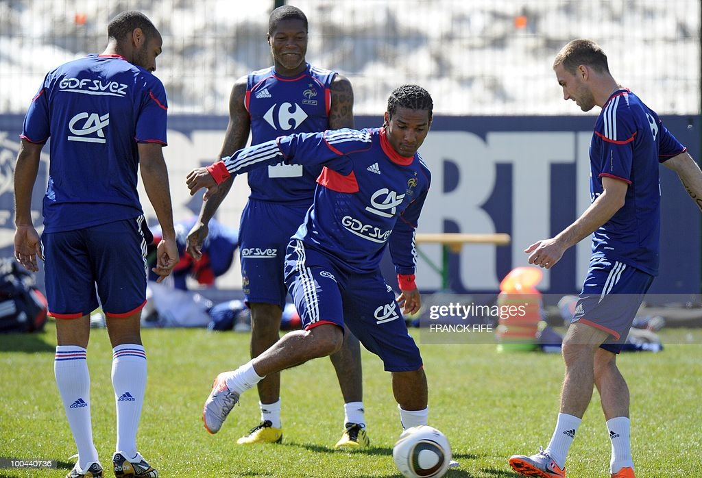 French national football team's midfielder Florent Malouda (C) controls the ball as forwards Thierry Henry (L) and Djibril Cisse (2ndL) watch during a training session, on May 24, 2010, near Tignes in the French Alps, as part of the preparation for the upcoming World Cup 2010. France will play against Uruguay in Capetown in its group A opener match on June 11.