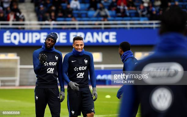 French national football team's midfielder Tiemoue Bakayoko and midfielder Corentin Tolisso react during a training session on March 20 in...