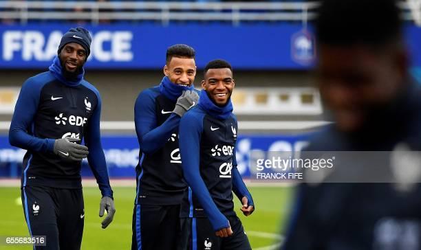 French national football team's midfielder Tiemoue Bakayoko midfielder Corentin Tolisso and midfielder Thomas Lemar react during a training session...