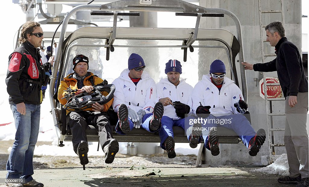French national football team's players Yoann Gourcuff (3rdL), press officer Francois Manardo (2ndR) and Thierry Henry sit on a ski lift upon their arrival in Tignes, French Alps, on May 20, 2010 after having spent the night with teammates at the top of the Tignes glacier, as part of their altitude training in preparation for the 2010 World cup in South Africa.
