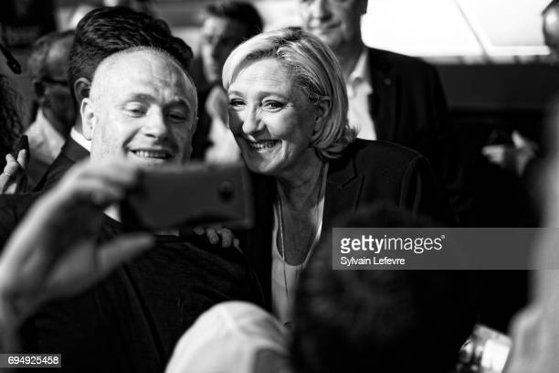 French National Front political party leader and candidate for French legislative elections Marine Le Pen poses for selfie with supporter after the...